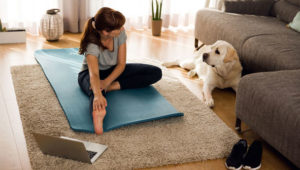 lady at home on rug with her laptop doing yoga looking at her dog